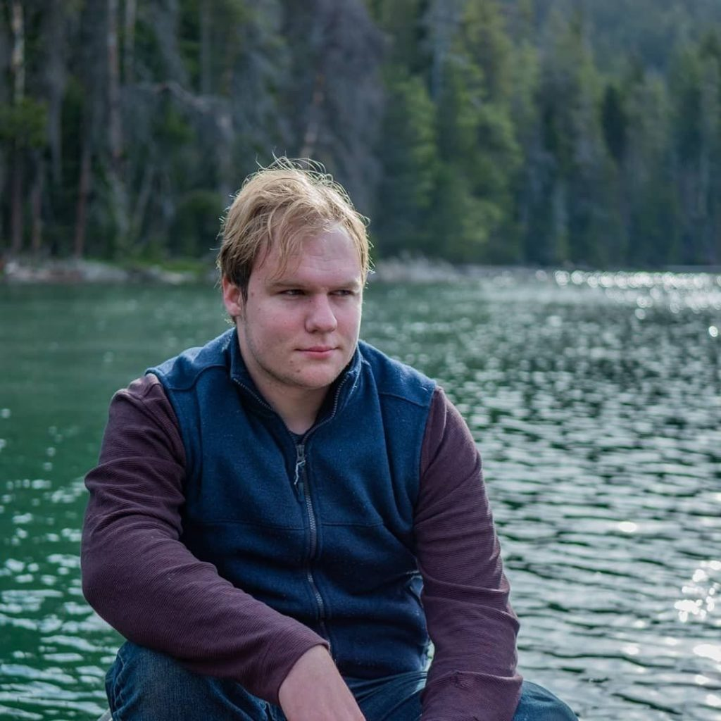 Nicholas sitting in a boat on a lake